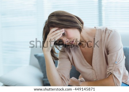 Sad young woman sitting on sofa at home