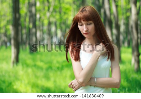 Sad young woman staying in the forest
