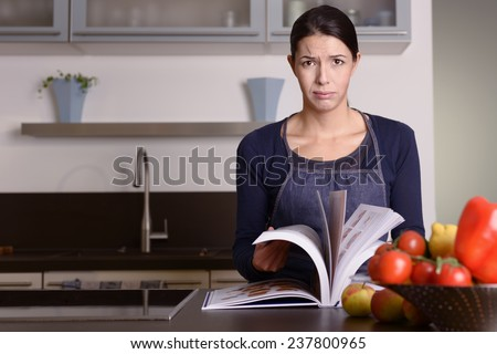 Sad Young Woman Wearing Apron Holding Recipe Book at the Kitchen While Looking at the Camera. - stock photo