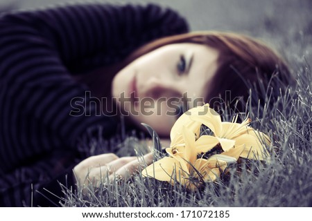 Sad young woman with a flowers lying on the grass - stock photo