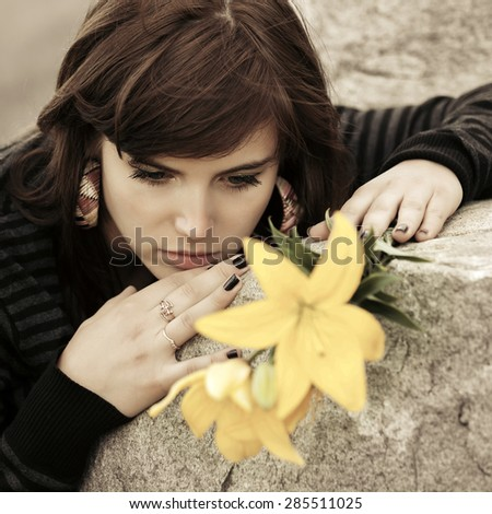 Sad young woman with a flowers lying on tombstone  - stock photo