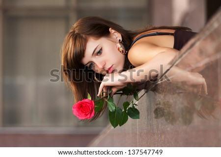 Sad young woman with a red rose - stock photo