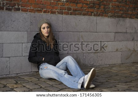 sad young woman with knitted hat , outdoors