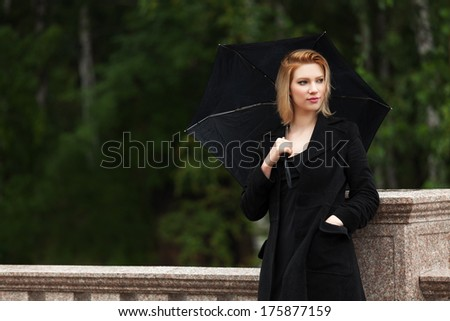 Sad young woman with umbrella in the rain - stock photo
