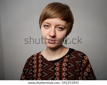 sad yuong  woman in poncho - stock photo