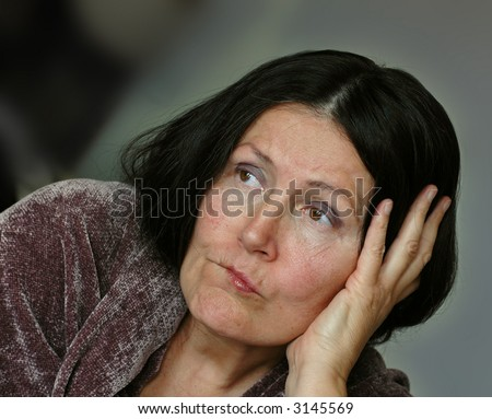 Saddened older woman, looking away from the camera. - stock photo