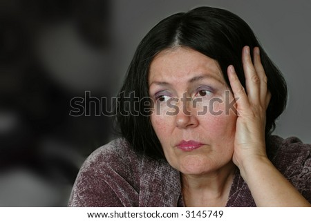 Saddened older woman sitting alone, propping her face with her hand - stock photo