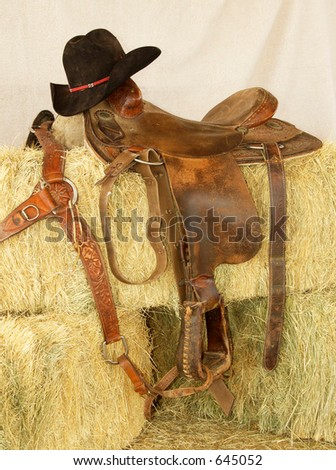Saddle and hat resting in hay bales. - stock photo