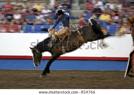 Saddle Bronc rider in the spotlight at a night rodeo (pan effect with slow shutter speed blur). - stock photo