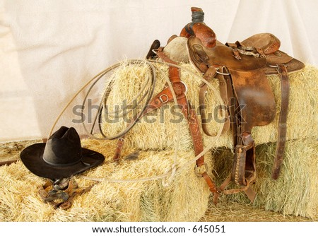 Saddle, hat, rope and gloves resting on hay bales. - stock photo