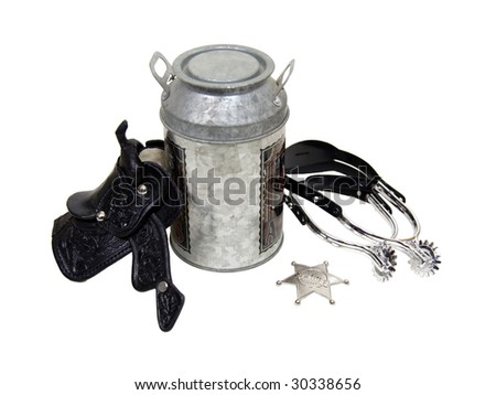Saddle made of heavy black leather for riding domestic horses, spurs, silver star, and a milk tin to make a cowboy kit - path included - stock photo