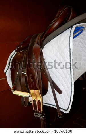 Saddle on a rack in a tack room, horseback riding equipment - stock photo