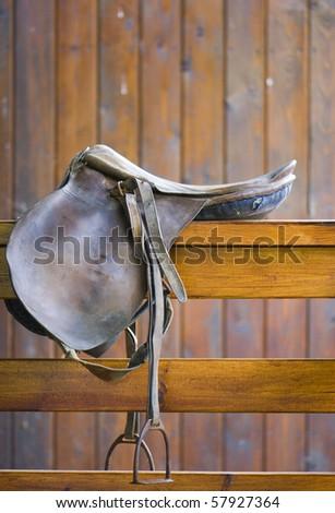 saddle on a wooden railing - stock photo
