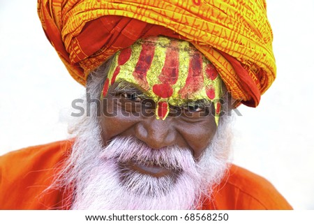 Sadhu at the ghats in Varanasi, India. With a pink beard from the traditional holi festival. - stock photo