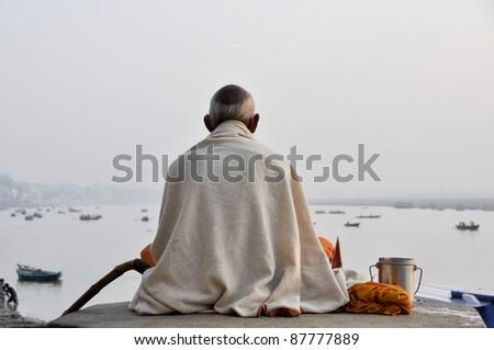 Sadhu praying at the ghats in Varanasi - stock photo