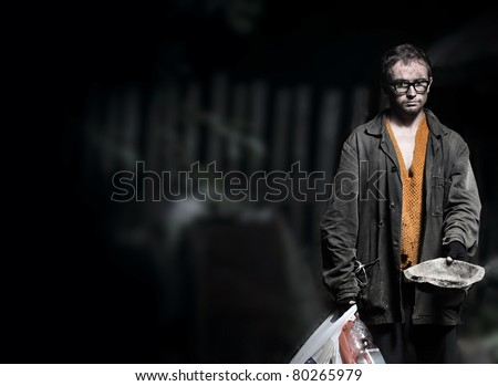 Sadly tramp in dirt and ragged clothes standing outdoor and asking help with a metal dish