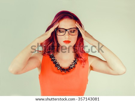 Sadness and depression. Closeup portrait stressed sad young woman eyes closed, face down hands touching head isolated green wall background.  Negative human emotion, expression reaction, body language - stock photo
