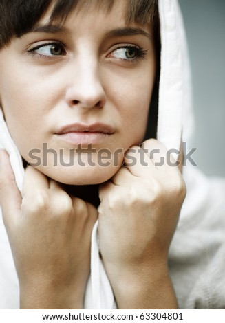 sadness in her eyes, close up of young woman with white hood, natural light, selective focus - stock photo