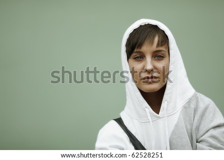 sadness in her eyes, young woman with white hood on urban wall background - stock photo