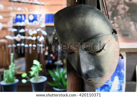 Sadness mask hanging on the wooden window                                - stock photo