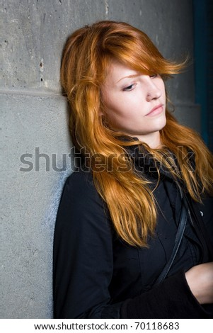 Sadness, moody portrait of a beautiful young redhead girl.