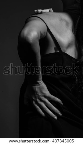 sadness young woman with naked back over black background. dark monochrome portrait of sexy body girl