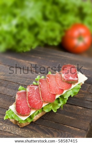 Sadwich with lettuce , cheese and dry meat on dark wooden table top - stock photo
