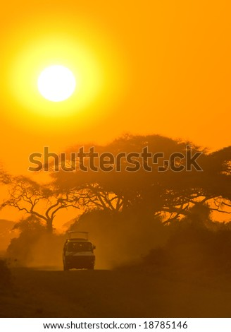 safari jeep driving through savannah in the sunset - stock photo