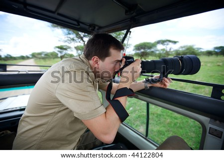 Safari vacation. Professional photographer taking picture on game drive in Tarangire national park, Tanzania.