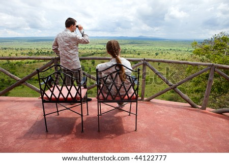 Safari vacation. Young couple in safari clothes observing beautiful national park of Tarangire in Tanzania from balcony in lodge.