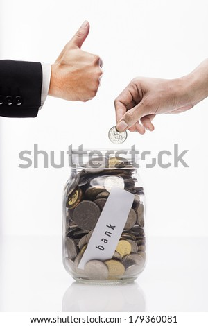 Safe Deposit concept,Hand putting Golden coins and seed in clear jar over white background