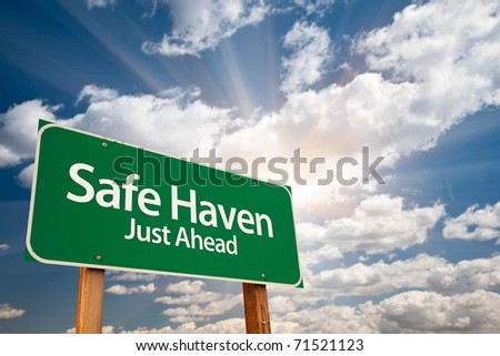 Safe Haven Green Road Sign with Dramatic Clouds, Sun Rays and Sky. - stock photo