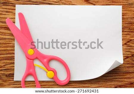 Safe scissors on blank white piece of paper - stock photo