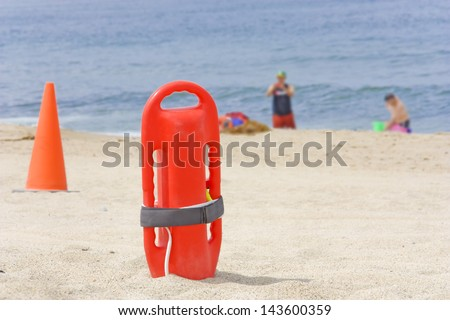 Safe summer fun, lifeguard nearby. Close up of red rescue buoy standing upright in the sand with orange safety cone.Blurry background with people, blue water. Shallow depth of focus on the rescue can. - stock photo