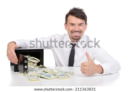 Safe with money. Happy young businessman in formalwear sitting at the table near the safe full of money while isolated on white - stock photo