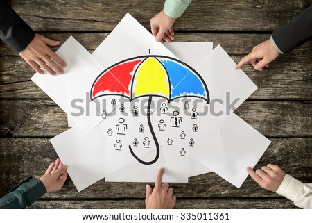 Safety and life insurance concept - six hands assembling a colourful umbrella sheltering many people icons drawn on white papers. - stock photo