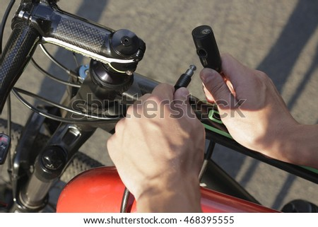 Safety and transport - close up of man fastening bicycle lock on street parking