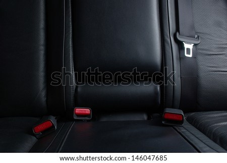 Safety buckle on the black leather seat in a car - stock photo