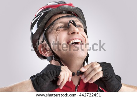 Safety Concept and Ideas. Male Caucasian Cyclist Checking Road Helmet. Wearing Glasses. Against White Background. Horizontal Image - stock photo