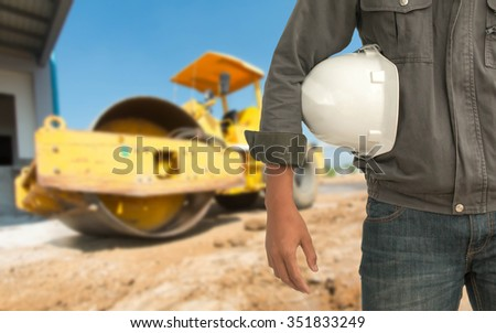 Safety engineering and a helmet resting on the details of the construction site with a bulldozer behind them. - stock photo