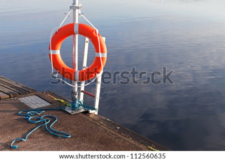 Safety equipment. Bright red lifebuoy on the pier - stock photo