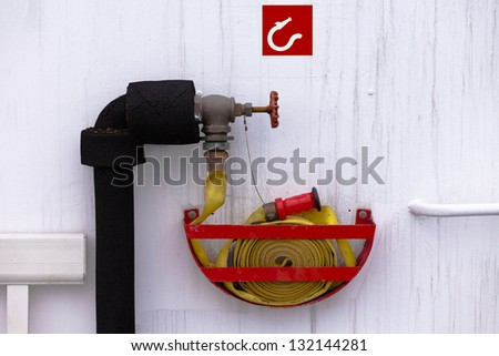 Safety equipment  rolled up yellow fire hose attached to water hydrant ready to be used in an fire emergency - stock photo