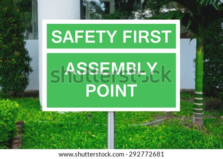 Safety first and assembly point on green signpost. For safety agenda in factory and industry. Assembly point is the place people would gather when safety alarm ringing.