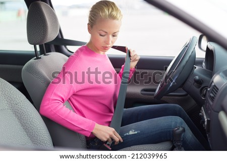 Safety first. Beautiful blonde caucasian lady fastening car seat belt.