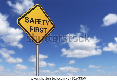 safety first road sign and blue sky - stock photo