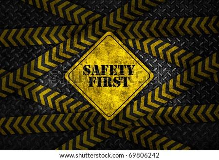 Safety first sign on dark cross caution strip background - stock photo
