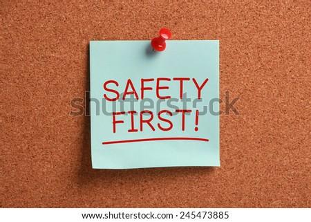 Safety First sticky note pinned on cork. - stock photo