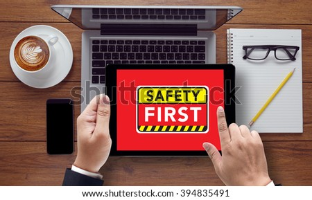 Safety First Warning concect on the tablet pc screen by businessman hands, top view, on the tablet pc screen held by businessman hands - online, top view - stock photo