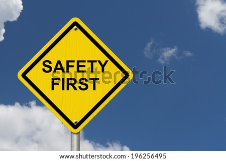 Safety First Warning Sign, Yellow warning sign with words Safety First Warning with blue sky background - stock photo