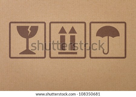 Safety, fragile icons on a cardboard parcel - stock photo